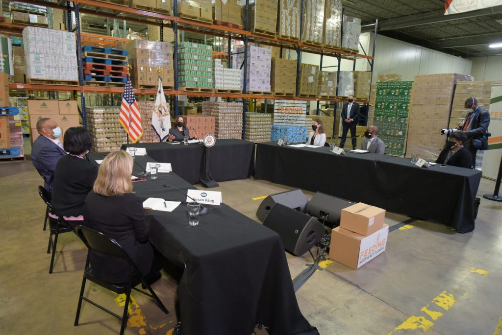 A photo of the interior of the Feeding Northeast Florida warehouse. There are 5 tables arranged in an upside-down U formation, with Vice President Harris at the head of the table. From bottom left to right, Susan King, Audrey Gibson, Al Lawson, Vice President Harris, Nikki Fried, Garrett Dennis, and Dr. Diana Greene are pictured.